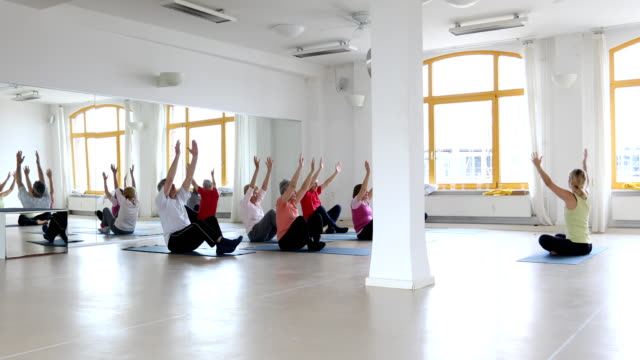 Instructor teaching senior people in yoga class video
