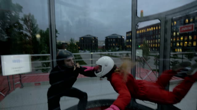 Instructor teaching young woman skydiving. Extreme parachuting in wind tunnel video