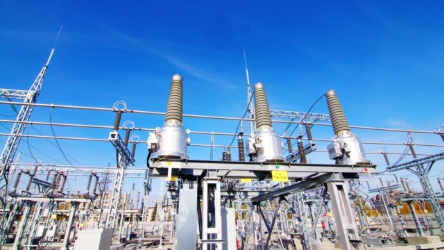 insulators and cables at electrical transmission substation - sottostazione elettrica video stock e b–roll