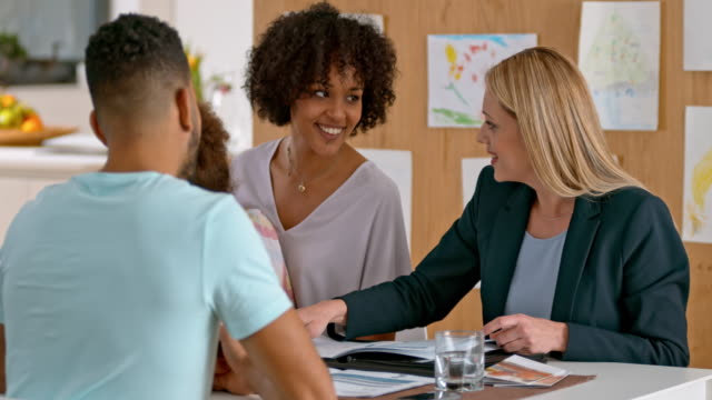 Insurance agent advising multi ethnic family at home video