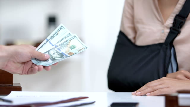 Insurance agent giving female worker in arm sling money compensation for trauma