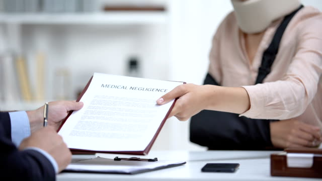 Insurance agent signing Medical negligence to accident victim with broken hand Insurance agent signing Medical negligence to accident victim with broken hand physical injury stock videos & royalty-free footage