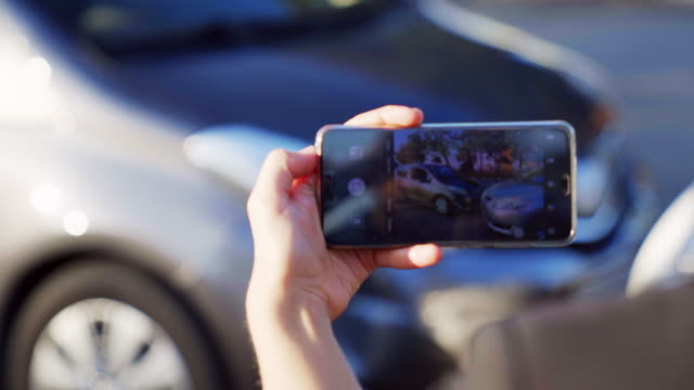 vídeos de stock e filmes b-roll de insurance agent taking photo of car accident on the smartphone. two broken cars after car accident standing on the road. close-up. 4k uhd - fotografar