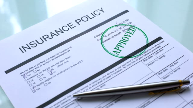 Insurance policy document approved, hand stamping seal on official paper closeup