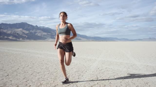 砂漠を通って実行しているたいまつ: 強烈な女性 - 耐久力点の映像素材/bロール