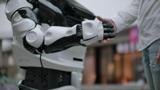 人工知能の人間と現代技術の相互作用科学者の男性の手を閉じるロボットアームを振る。ロボットと人間の手が握手で合流します。友人との出会いと挨拶 - 指点の映像素材/bロール