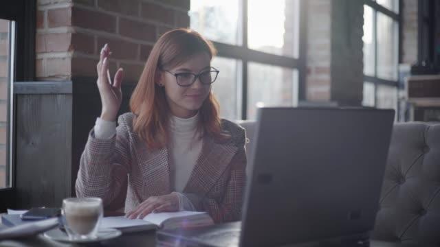 interaktive ausbildung, junge mädchen spezialist für brille für das online-studium am laptop sitzend am tisch machen notizen in notebook im café - webinar stock-videos und b-roll-filmmaterial