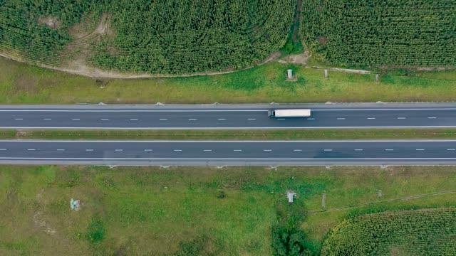 stockvideo's en b-roll-footage met intercity speed highway met bewegende vrachtwagen met cargo luchtfoto - bovenkleding