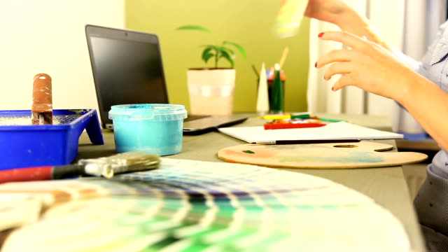 Interior design, renovation and decoration concept - woman working with color samples for selection in her office video