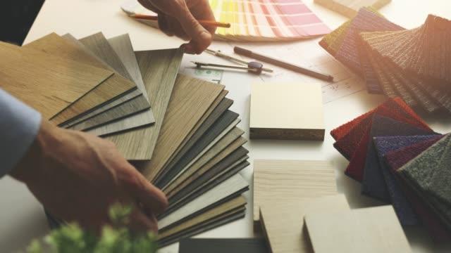 inredningsarkitekt välja golv och möbler material från prover för heminredningsprojekt i office - alternativ bildbanksvideor och videomaterial från bakom kulisserna