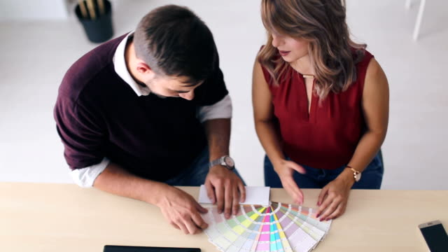 Interior designers pointing at colour charts video