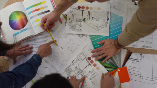 Interior designers working together on a project looking at a color swatch and blueprints Interior designers working together on a project looking at a color swatch and blueprints - High angle view interior designer stock videos & royalty-free footage