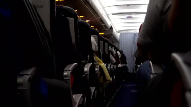 Interior de avión con pasajeros en el asiento durante el vuelo. Sillas en el pasillo - vídeo