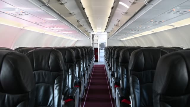 4k interior of commercial airplane cabin with black and red passenger seats. - kabina filmów i materiałów b-roll
