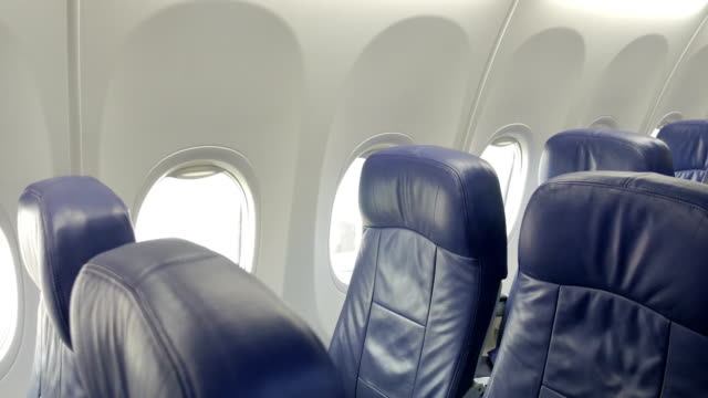 interior of commercial airplane cabin with blue passenger seats. - sedili aereo video stock e b–roll
