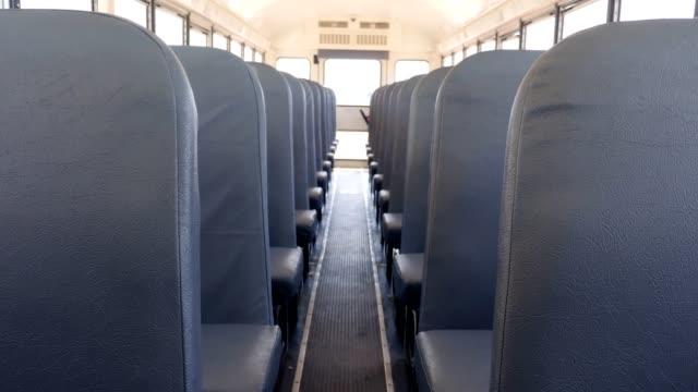 Interior of empty school bus Rows of empty seats on a school bus. school buses stock videos & royalty-free footage