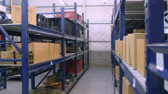 Interior of factory warehouse with long shelves Dolly shot of long shelves industrial warehouse with boxes and containers. Interior of factory warehouse. storage room stock videos & royalty-free footage