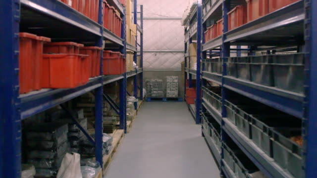 Interior of factory warehouse with long shelves Dolly shot of long shelves industrial warehouse with boxes and containers. Interior of factory warehouse. Corridor of storage room. storage room stock videos & royalty-free footage