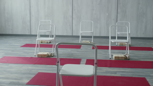 vídeos de stock e filmes b-roll de interior of fitness studio with chairs and yoga mats - chair