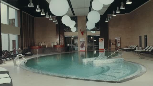 vídeos de stock, filmes e b-roll de interior do luxuoso centro de spa. spa de natação indoor com jacuzzi, piscina, cadeiras de convés. - comodidades para lazer