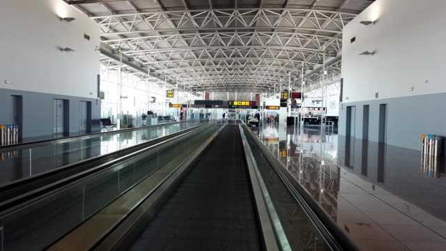 interior of modern airport Moving slowly on travelator, interior of modern airport barren stock videos & royalty-free footage