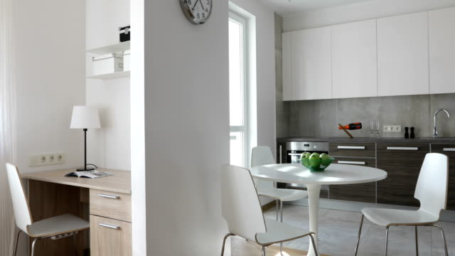 4K. Interior of modern apartment in scandinavian style with kitchen and workplace. Motion panoramic view 4K. Interior of modern apartment in scandinavian style with kitchen and workplace. Motion panoramic view. interior designer stock videos & royalty-free footage
