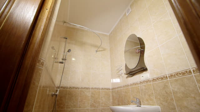 Interior of small bathroom with sink shower and toilet video