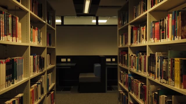 Interior of the library passages with shelves full of books n the light room. Dolly move camera forwards