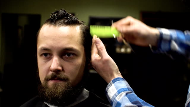 Interior shot of working process in modern barbershop. Close-up portrait of attractive young man getting trendy haircut. Male hairdresser serving client, making haircut using metal scissors and comb video