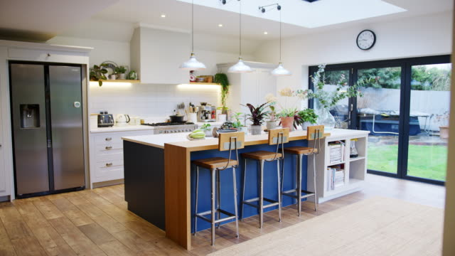 Interior view of beautiful kitchen with island counter and house plants in family home - shot in slow motion Interior view of beautiful kitchen with island counter and house plants in family home - shot in slow motion kitchen stock videos & royalty-free footage