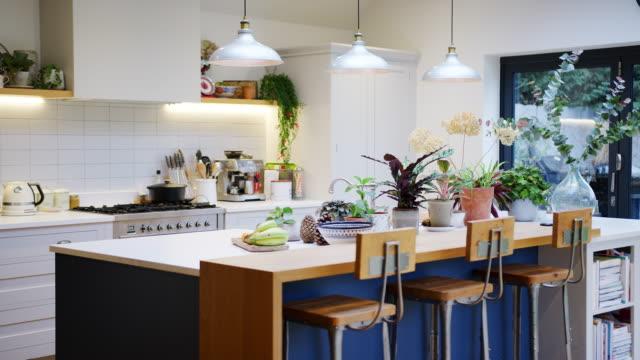 stockvideo's en b-roll-footage met binnenlandse mening van mooie keuken met eilandteller en huisinstallaties in familiehuis - dat in langzame motie wordt ontsproten - modern