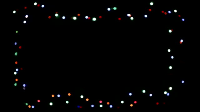 intermittent colored christmas lights of many colors in progressive blur, on a black background, to form a decorative frame. - christmas lights стоковые видео и кадры b-roll