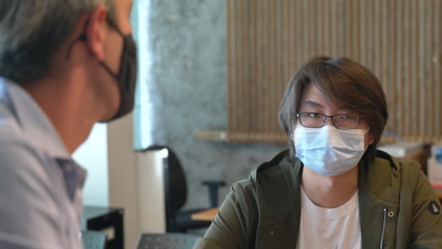 International student doing course selection with faculty member An Asian male international student meeting with a university faculty member to discuss course selection while wearing protective face masks to avoid the transfer of germs. guidance stock videos & royalty-free footage