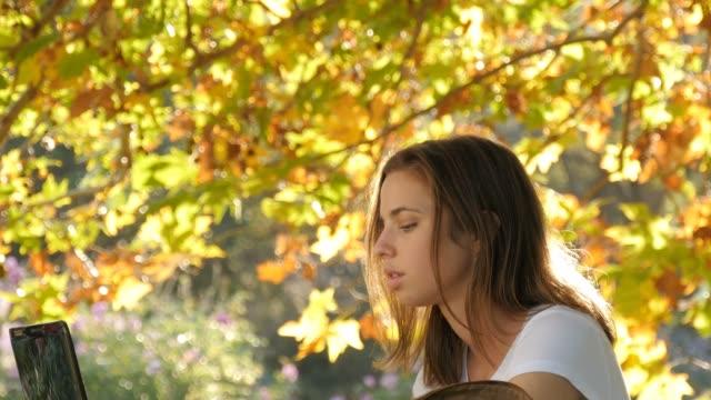stockvideo's en b-roll-footage met internationale student studeren met boeken en laptop onder mooie herfst boom - omgeving