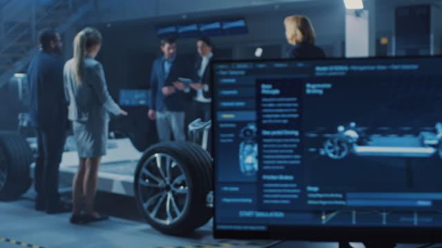 международная команда инженеров автомобильного дизайна представляя футуристический автономный электрический автомобиль платформы шасс� - моторное транспортное средство стоковые видео и кадры b-roll