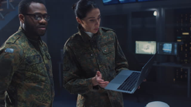 international team of military personnel have meeting in top secret facility, female leader holds laptop computer talks with male specialist. people in uniform on strategic army meeting - armia filmów i materiałów b-roll