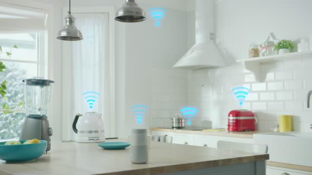 concetto di internet of things: moderna cucina bianca elegante piena di elettrodomestici da cucina high-tech con iot, logo wireless su di essi. digitalizzazione, visualizzazione di dispositivi elettronici per la casa connessi - elettrodomestico attrezzatura domestica video stock e b–roll