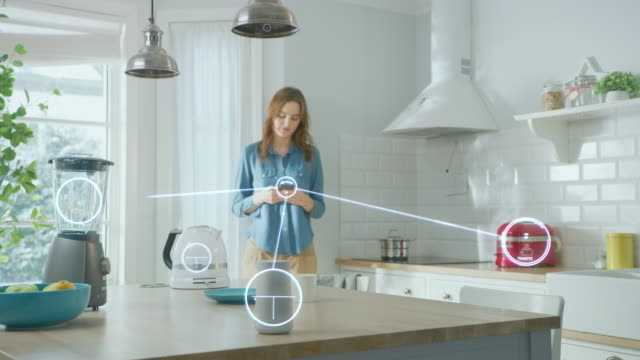 Internet of Things Concept: Young Woman Using Smartphone in Kitchen. She controls her Kitchen Appliances with IOT. Graphics Showing Digitalization Visualization of Connected Home Electronics Devices Internet of Things Concept: Young Woman Using Smartphone in Kitchen. She controls her Kitchen Appliances with IOT. Graphics Showing Digitalization Visualization of Connected Home Electronics Devices home icon stock videos & royalty-free footage