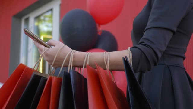 vídeos y material grabado en eventos de stock de compra en internet, los clientes mujer usa smartphone para comprar y pagar en línea en temporada de descuentos están para arriba, paquetes colgando por parte - black friday sale