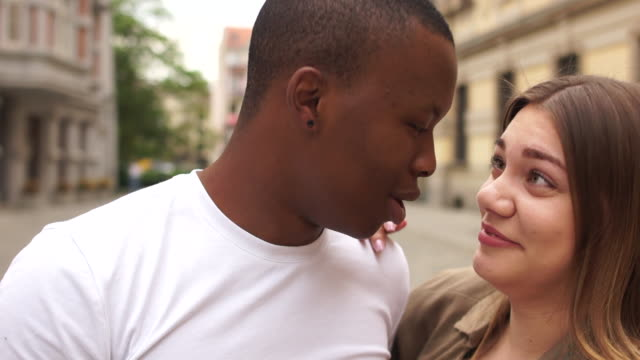 Interracial couple in love dancing on the city street. Boy and girl students, mixed race couple dancing and laughing. Happy couple african guy and caucasian woman
