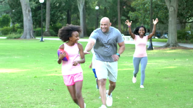 Interracial family in park, girl running with football