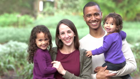 Interracial family standing outdoors together A young Interracial family with two cute little girls standing outdoors, smiling at the camera. The children are 3 year and 16 months. family stock videos & royalty-free footage