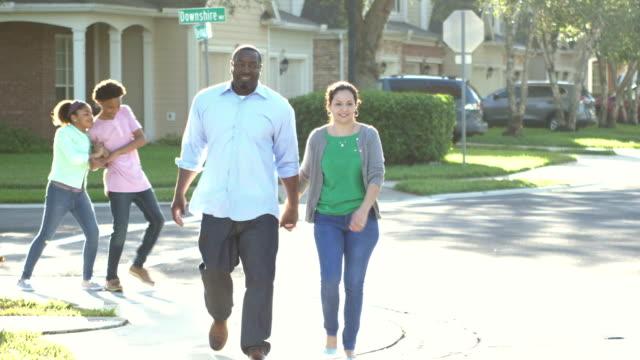 Interracial family taking walk, children playing