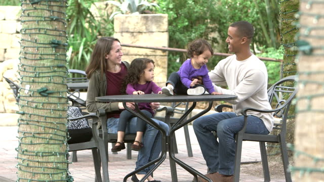 Interracial family with two girls sit at outdoor cafe video