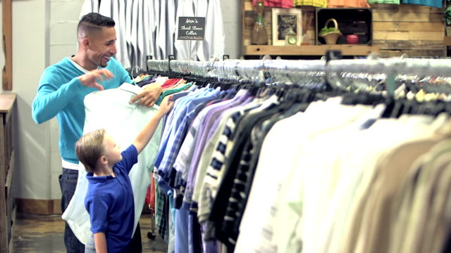 Interracial father and son shopping in clothing store video