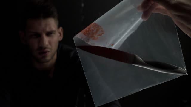 vidéos et rushes de interrogateur montrant un couteau avec du sang comme une preuve de meurtre - lame