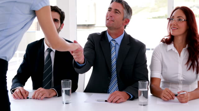 Interview panel shaking hands with applicant video