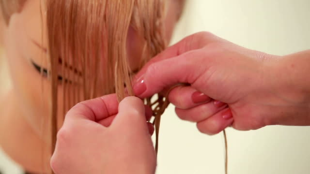 Interweaving of strands of hair. Hairstyle from hair. Close up. White Process of collecting the hair in the hair style by weaving the strands, girl doing hairstyle synthetic mannequin on the wet hair, barber weaves a braid on the head of the four strands, on a white background, close up doll stock videos & royalty-free footage
