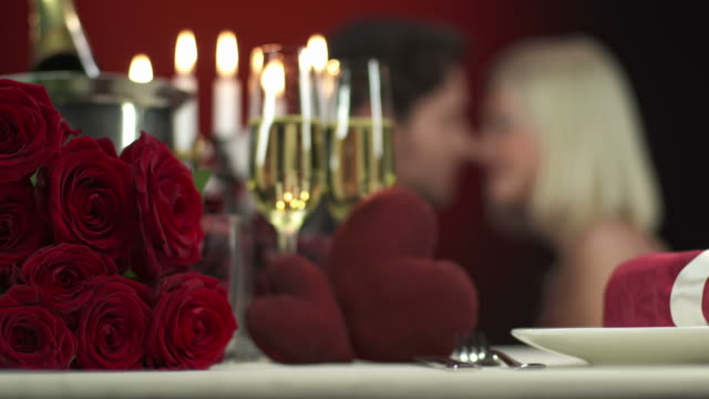 HD: Intimate Couple On Valentine's Day HD1080p: Front focus of a table perfectly decorated for romantic Valentine's dinner with blurred background where young couple softly touching and kissing each other. bunch stock videos & royalty-free footage
