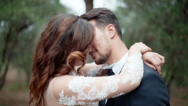 intimate kiss of young couple in love, affection and passion from the first sight. married couple embracing and touching each other with pleasure, just married couple in love concept - young couple wedding friends video stock e b–roll